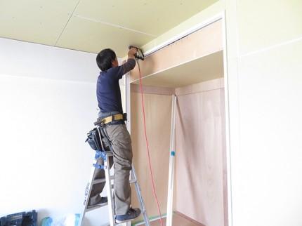 壁に作業する職人さんの写真